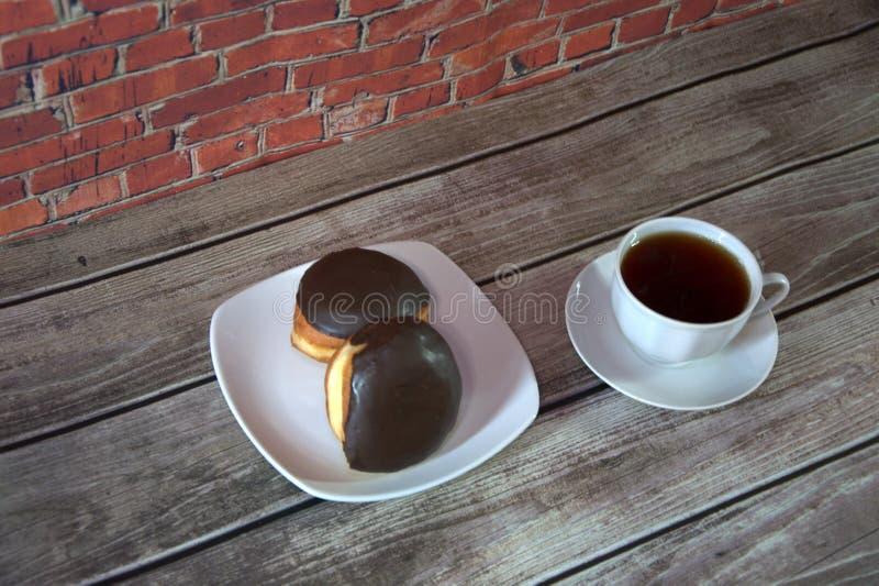 Чашка черного чая на поддоннике и плите с 2 donuts в лож замороженности шоколада на деревянном столе против кирпичной стены : стоковые фото