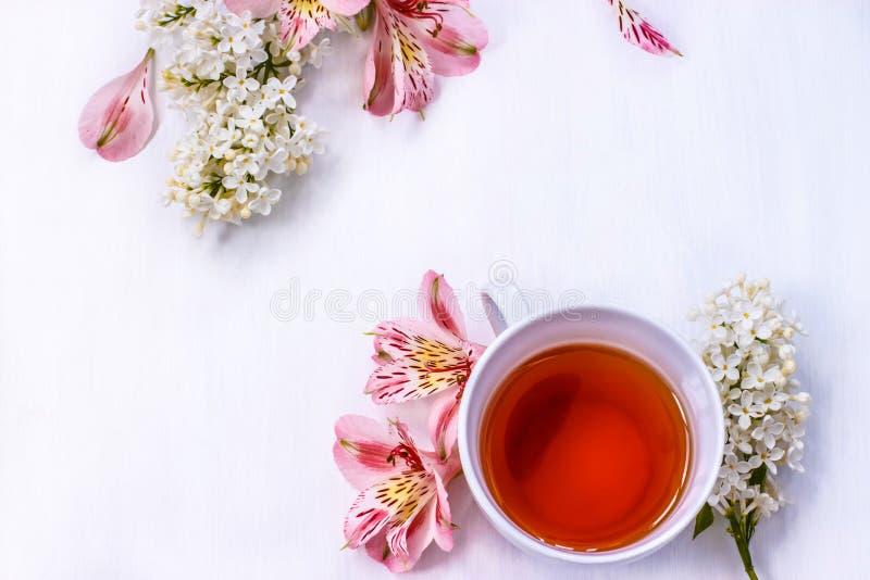 Чашка черного чая с букетом сирени на белой таблице стоковое изображение