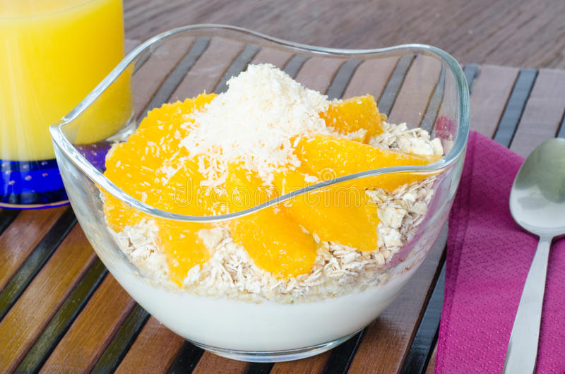 Чашка югурта с свежим muesli апельсина и кокоса стоковое фото