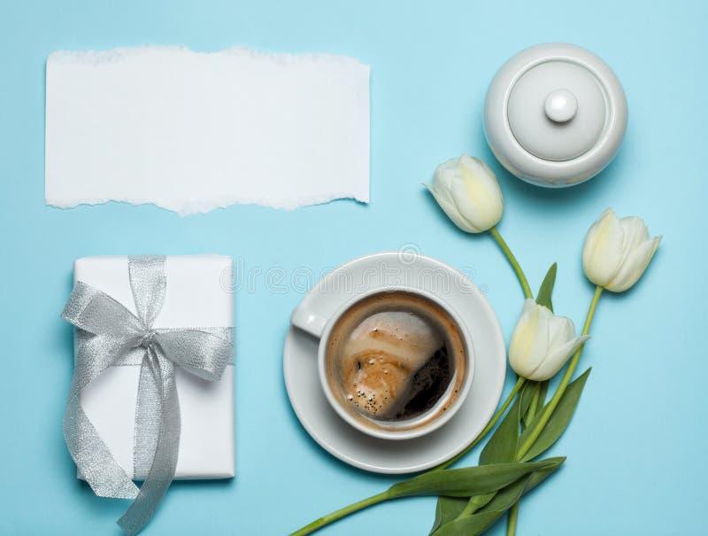 Чашка coffe и белые тюльпаны на голубой предпосылке стоковая фотография
