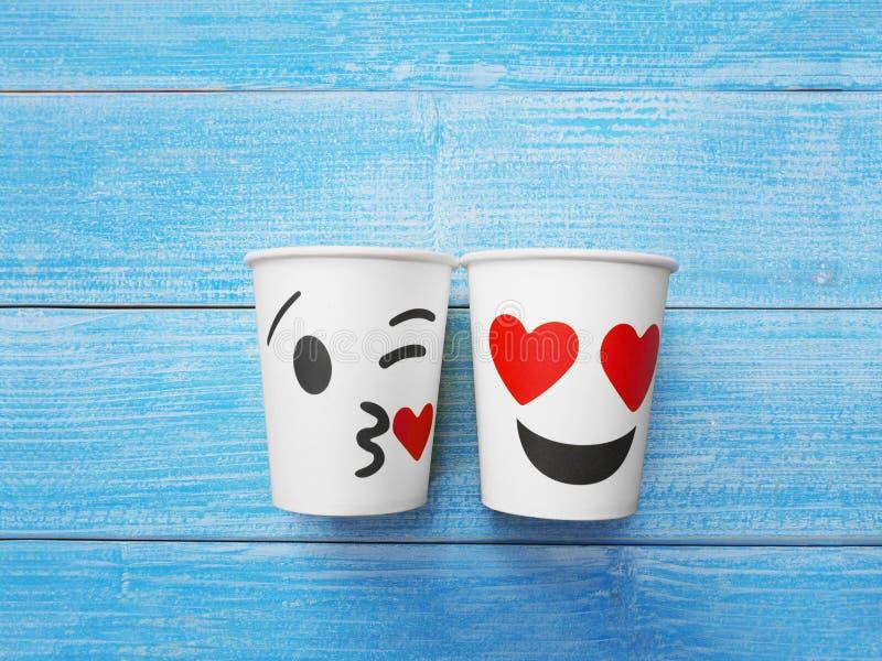 2 чашки белой бумаги с стороной целуют и усмехаются на деревянной таблице стоковая фотография