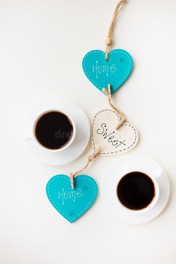 2 чашки кофе на таблице которая говорит домой стоковое фото