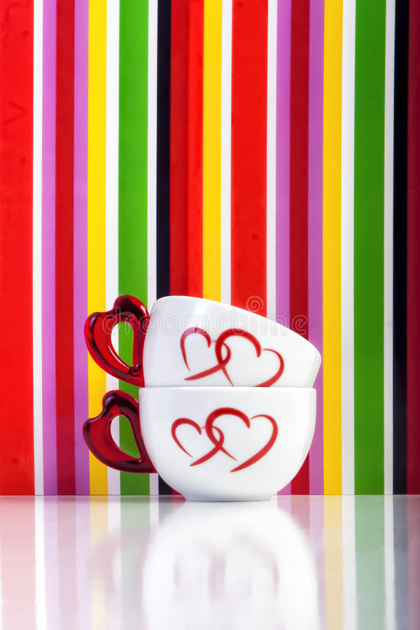 2 чашки с сердцами на красочной предпосылке нашивок стоковое изображение