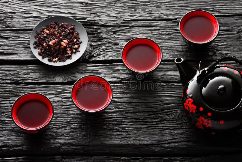 Чашки чаю и чайник на черном деревянном столе стоковые фото