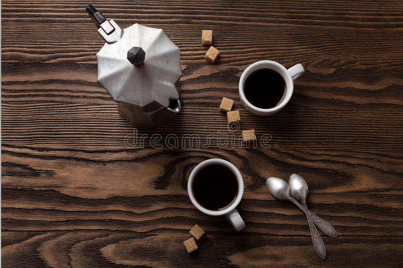 2 чашки эспрессо с частями тростникового сахара и итальянской кофеварки на таблице стоковые фото