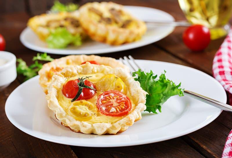 Чеддер, tartlets томатов на деревянной предпосылке Миниые расстегаи стоковые фото