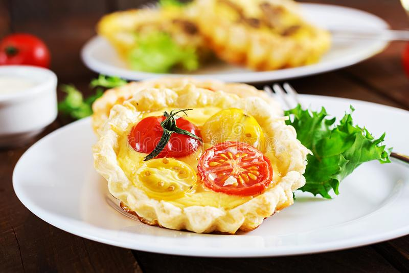 Чеддер, tartlets томатов на деревянной предпосылке Миниые расстегаи стоковые изображения