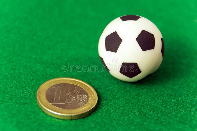 Чеканьте одно евро и футбольный мяч сувенира на зеленой предпосылке Деньги и спорт концепции, держа пари на футболе, коррупция и  стоковые изображения rf