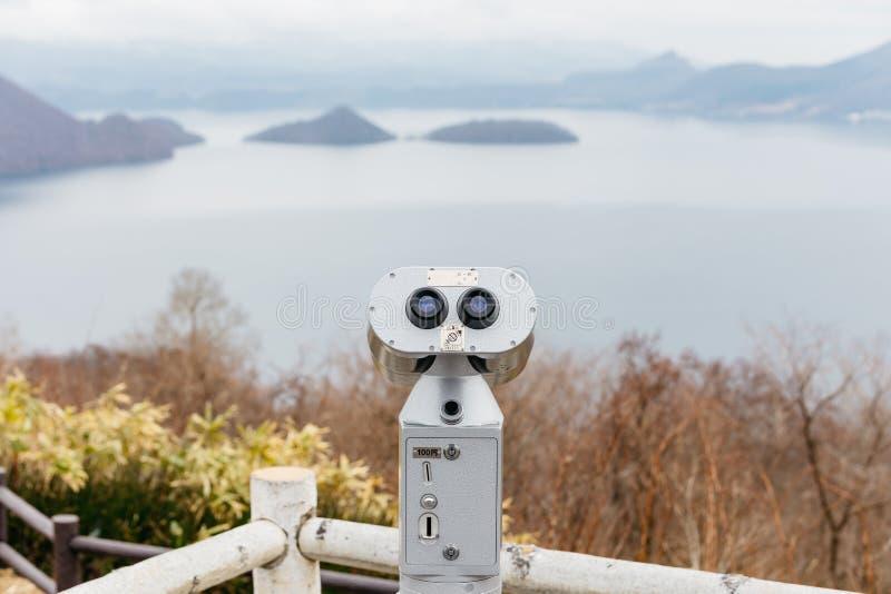 Чеканьте управляемые бинокли на озере Toya для видеть деталь горы и озере в Хоккаидо, Японии стоковая фотография rf
