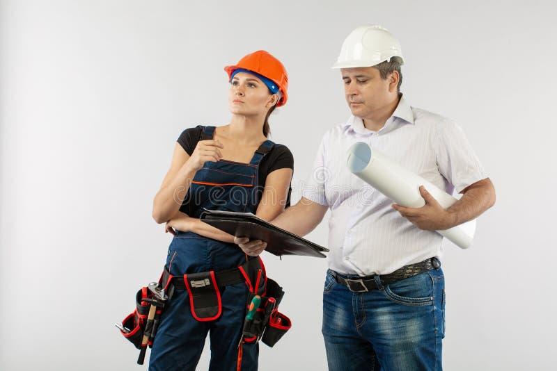 Человек архитектора нося светокопии женщины трудной шляпы или построителя шлема и сотрудника рассматривая стоковое фото