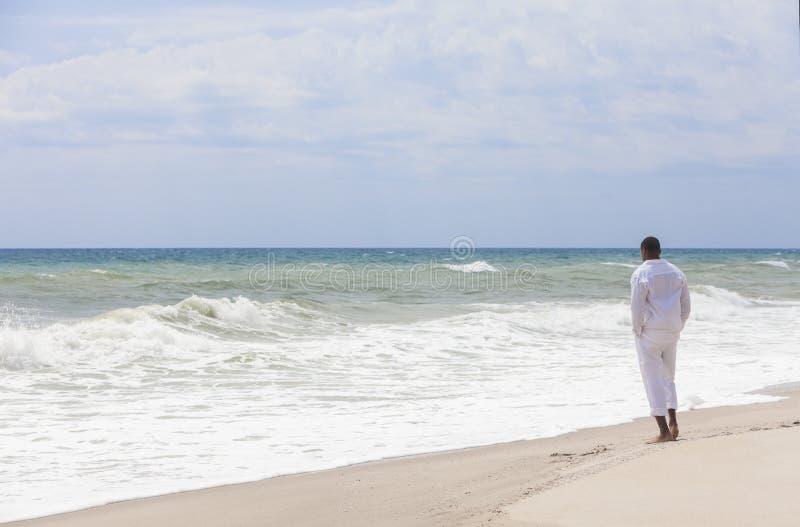 Человек афроамериканца самостоятельно на пляже стоковые изображения rf