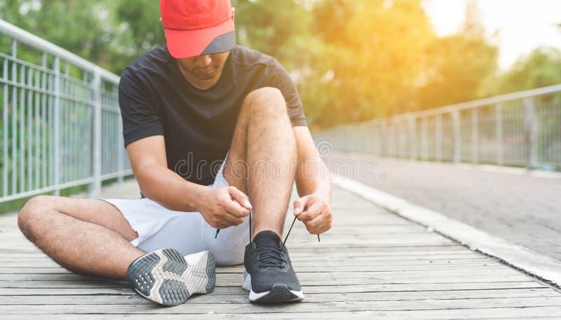 Человек бегуна молодой связывая шнурок получая готовый для гонки на, который побежали следе Здоровые концепции фитнеса, разминки, стоковые изображения