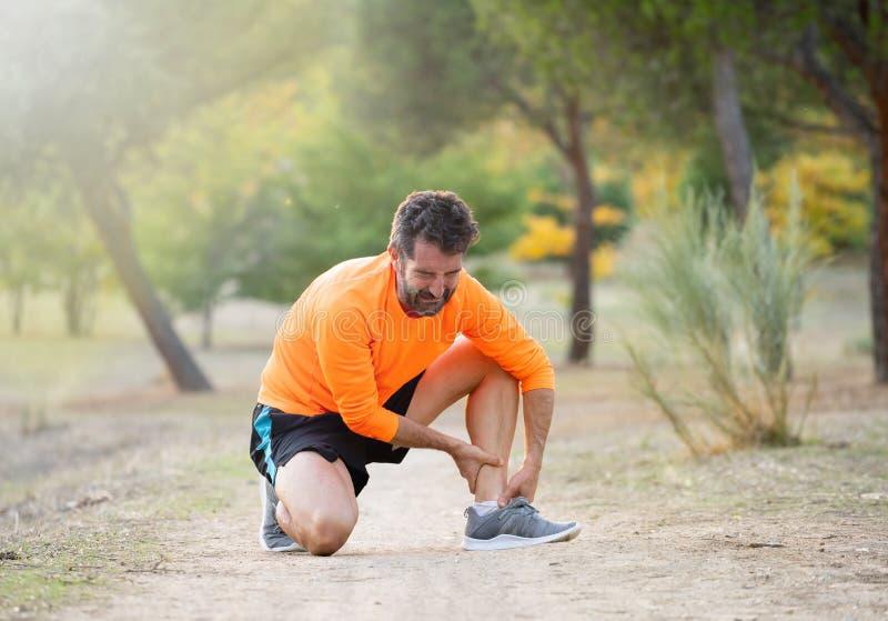 Человек бегуна Jung касаясь ноге в боли должной к sprained сломленной или переплетенной лодыжке пока бегущ стоковые фото