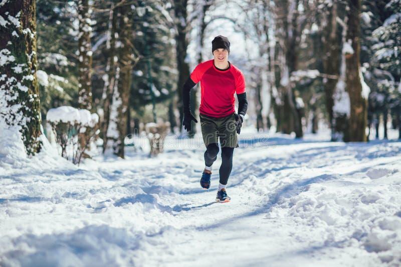 Человек бежать на зиме в парке стоковые изображения rf