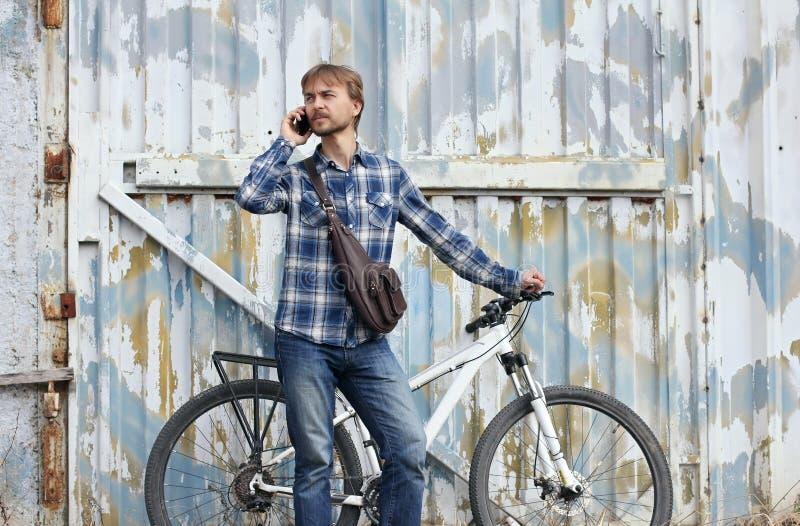 Человек битника бородатый с велосипедом и кожаная сумка, беседы на умном стоковое изображение rf