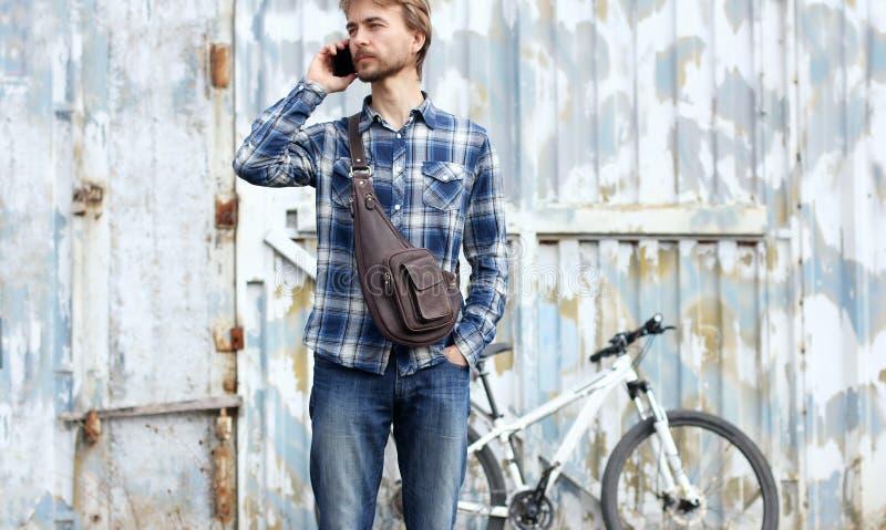 Человек битника бородатый с современной кожаной сумкой говорит на smartphone стоковое изображение rf