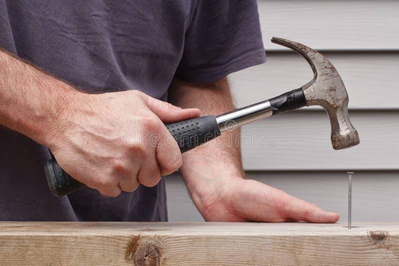 Человек бить молотком ноготь молотком стоковые изображения rf