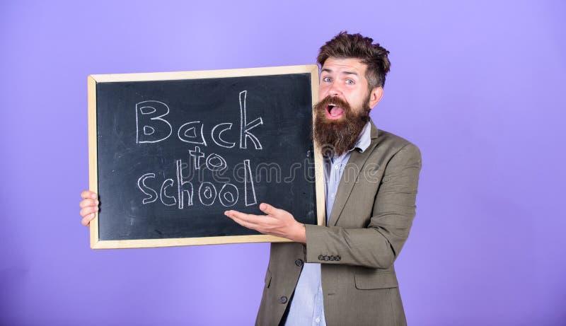 Человек бородатый в официальной носке держит классн классный с текстом назад в школу Одежда для учителей Реклама сезона школы стоковое фото rf