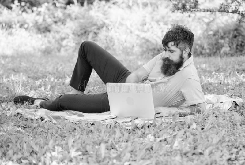 Человек бородатый с предпосылкой природы луга ноутбука ослабляя Писатель ища окружающая среда природы воодушевленности стоковая фотография rf