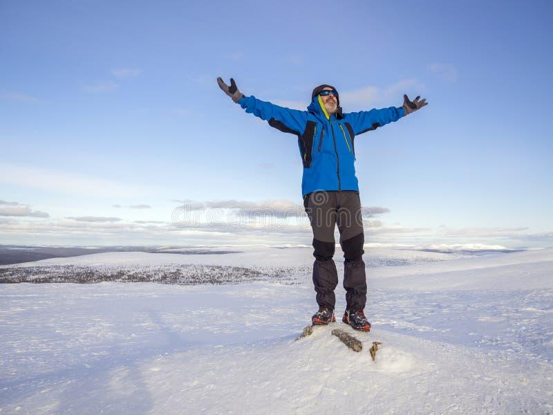 Человек вверху снежная гора с его руками вверх стоковая фотография rf