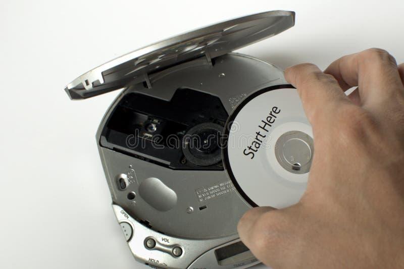 Человек вводит компактный диск в чд-плеер с сообщением старта здесь стоковое изображение rf