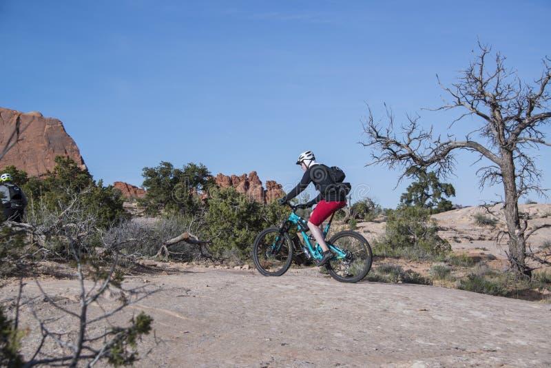 Человек велосипедиста горы ехать его жирный велосипед автошины на slickrock в сценарной пустыне Moab, Юты стоковое фото rf