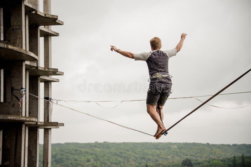 Человек вид сзади идя на веревочку slackline стоковые фото