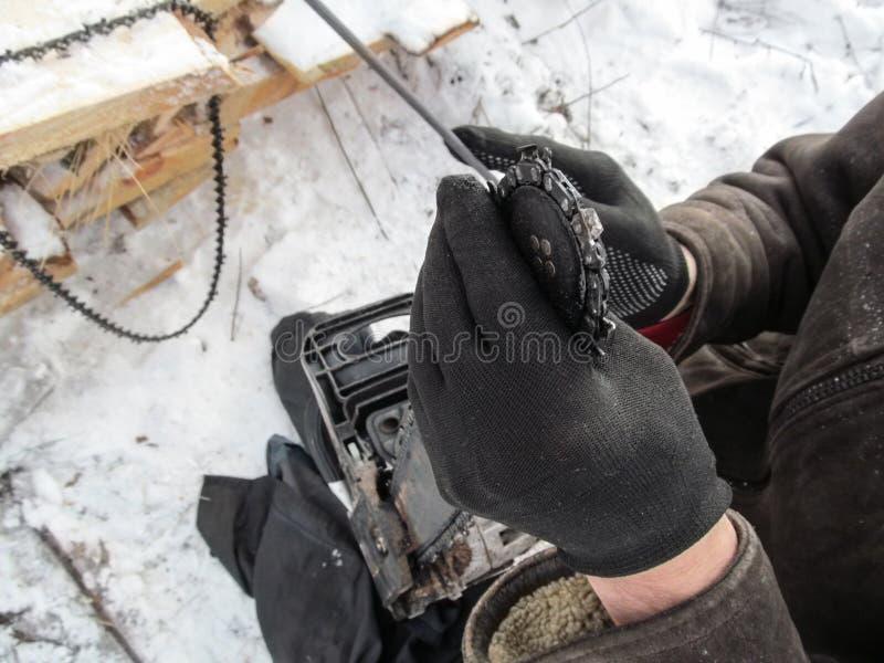 Человек вручную точит одну цепь на цепной пиле, и на деревянной планке висит запасную цепь в стороне стоковые изображения