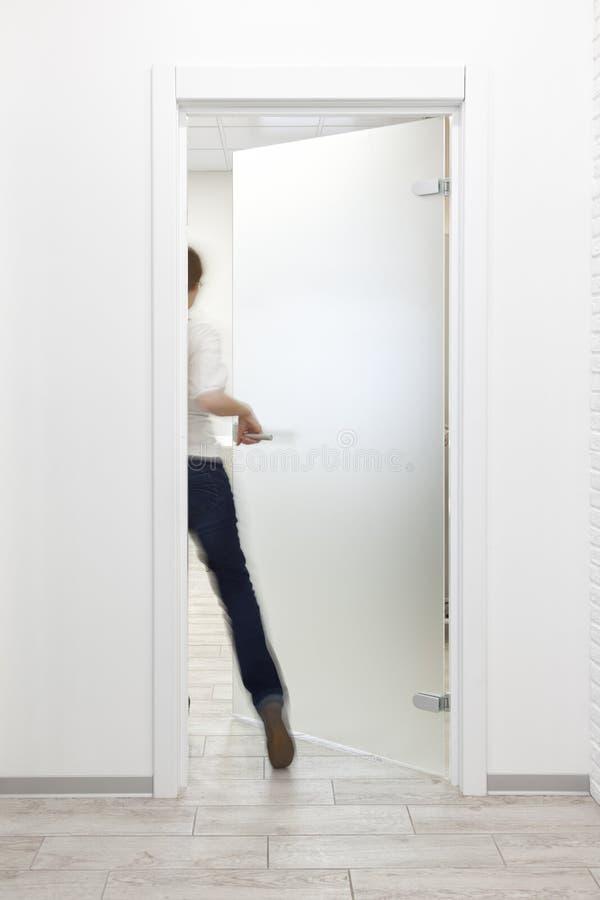 Человек входя в комнату в офис с минималистским белым интерьером стоковое изображение