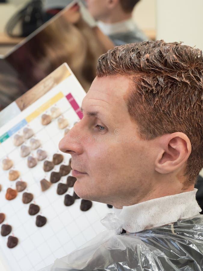 Человек выбирает краску волос Расцветка серых волос стоковые фотографии rf