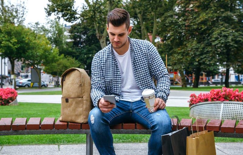 Человек выглядя мобильным усаживанием на стенде стоковое изображение