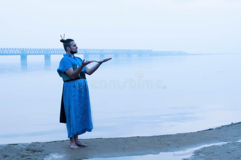 человек в голубом положении кимоно на речном береге в тумане, держа деревянную ручку и смотря прочь стоковая фотография rf