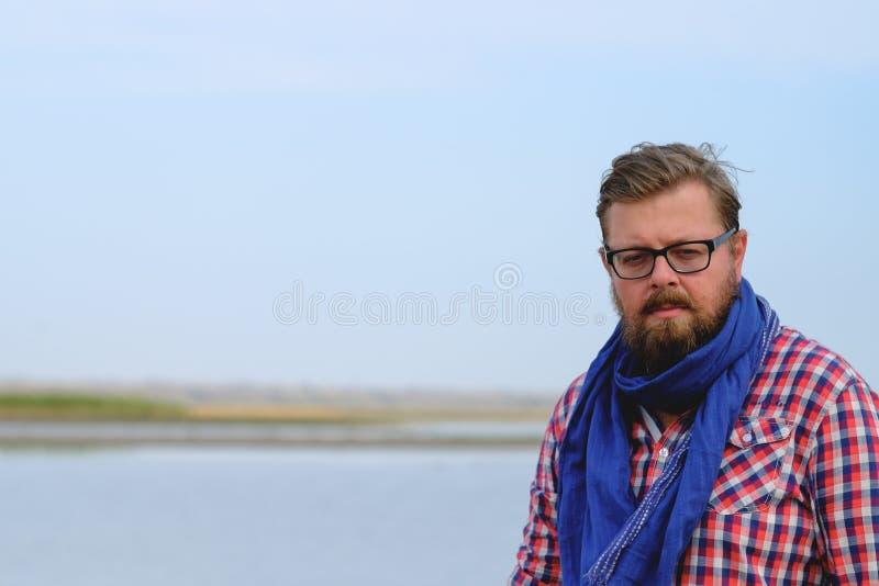 Человек в голубых джинсах и красной рубашке идя река стоковое изображение