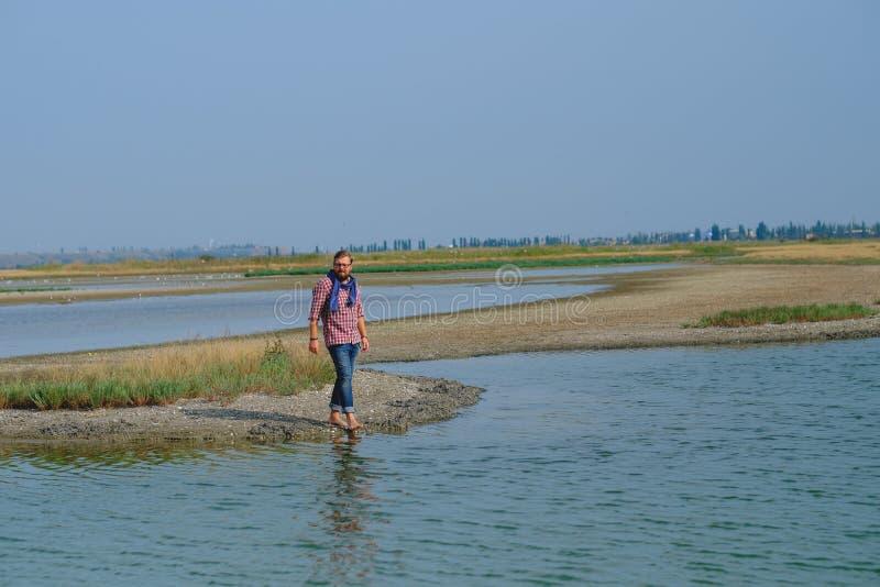 Человек в голубых джинсах и красной рубашке идя река стоковые изображения rf