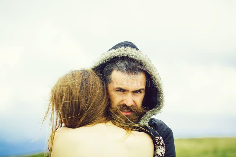 Человек в девушке объятий клобука стоковые фотографии rf