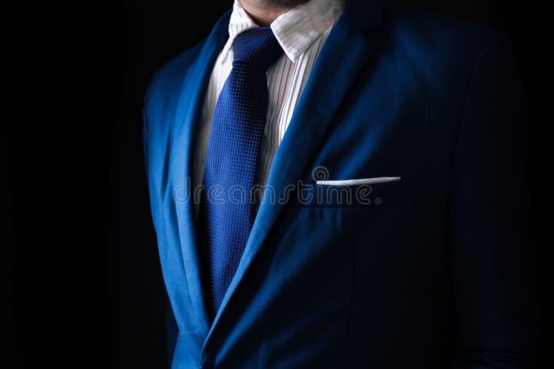 Человек в деловом костюме, бизнесмен на черной предпосылке стоковое изображение