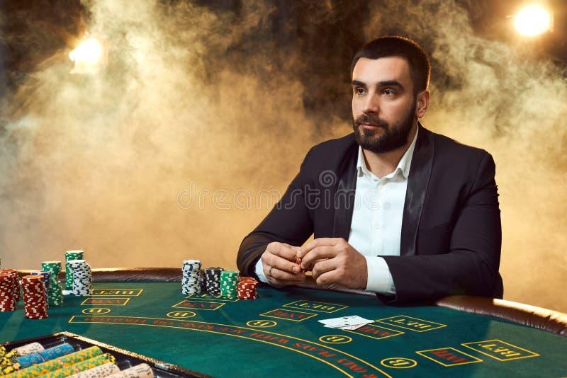 Человек в деловом костюме сидя на таблице игры Мужской игрок Страсть, карточки, обломоки, спирт, кость, играя в азартные игры, ка стоковые изображения rf