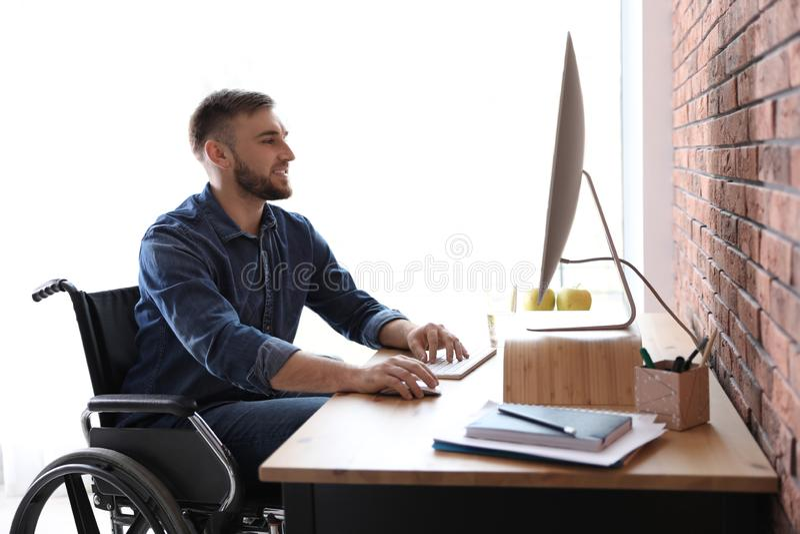 Человек в деятельности кресло-коляскы с компьютером на таблице стоковое фото