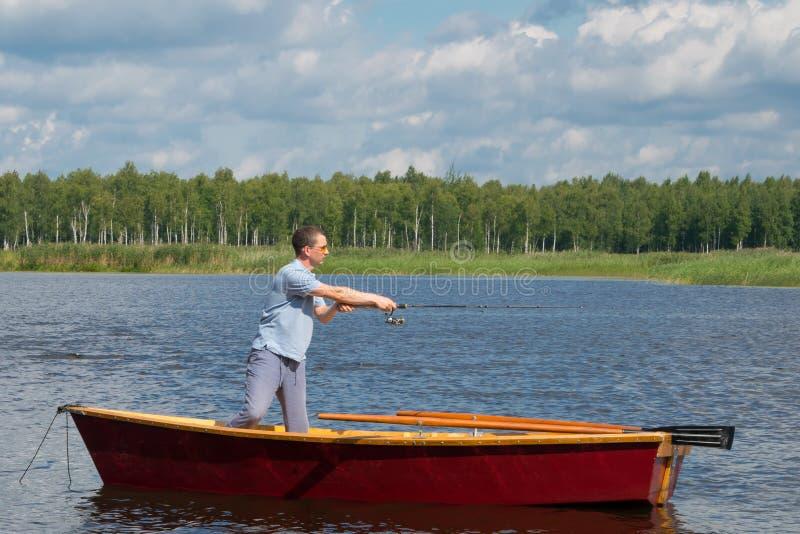 Человек в желтых стеклах, в шлюпке с веслами, в центре озера, держит удя поляка для того чтобы уловить большую рыбу, между a стоковые фотографии rf