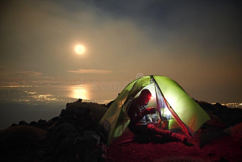 Человек в загоренном побережье взгляда шатра с полнолунием ночи стоковая фотография