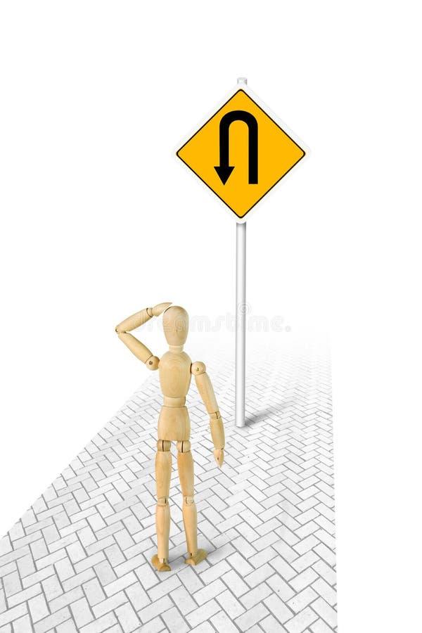 Человек в запутанности стоя перед поворачивает назад дорожный знак стоковое изображение rf