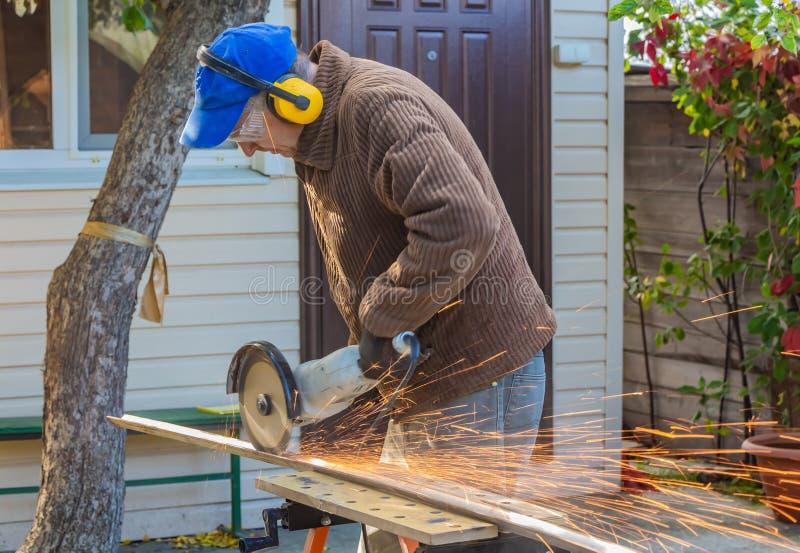 Человек в защитных стеклах и желтых протекторах уха и коричневом металле отрезков куртки используя большую белую угловую машину стоковое фото rf