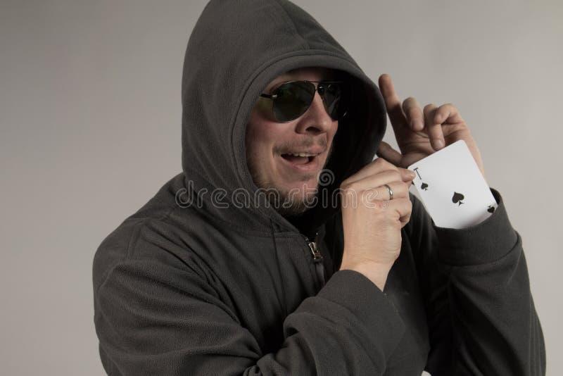 Человек в клобуке держит игральные карты в его руках стоковые фото