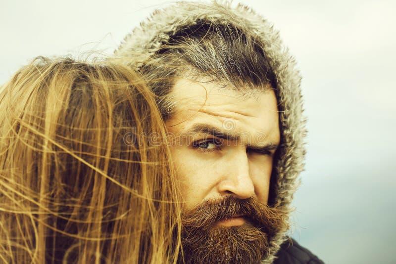 Человек в клобуке обнимает девушку стоковые изображения