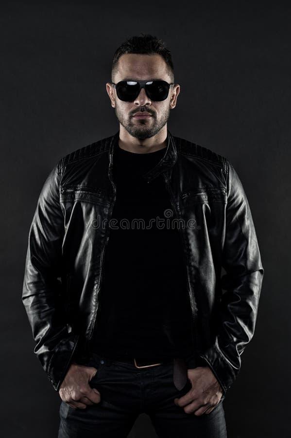 Человек в кожаной куртке и джинсыах Бородатый человек в ультрамодных солнечных очках Фотомодель в одеждах непринужденного стиля М стоковые изображения rf