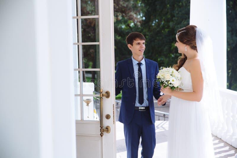 Человек в костлявом дела стильное тщательно раскрывает дверь к славной девушке в платье свадьбы и букет цветков стоковая фотография rf