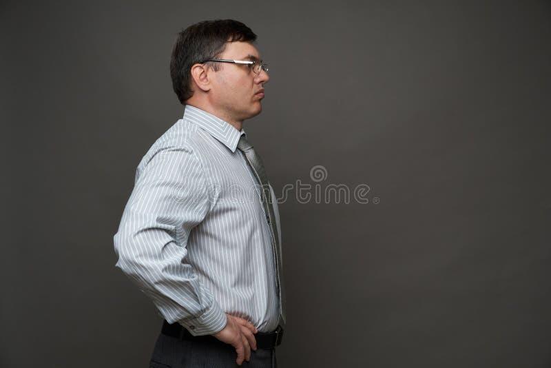 Человек в костюме бизнесмена, позирующего в студии на сером фоне, в очках, в светлой полосатой рубашке и галстуке - казуальный оф стоковое изображение rf
