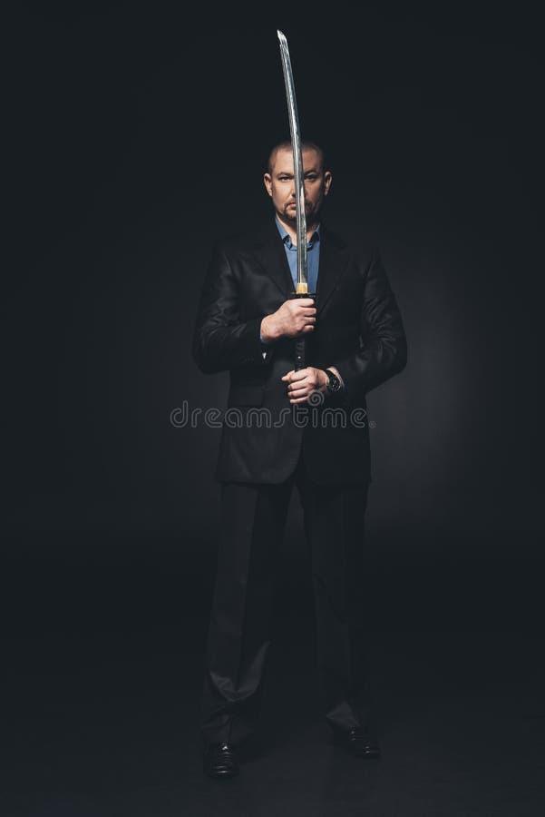 человек в костюме держа японскую шпагу katana перед его стороной стоковое фото rf