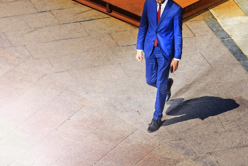 Человек в костюме идет на квадрат к успеху стоковое изображение
