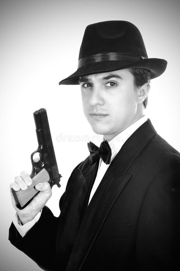 Человек в костюме рисует личное огнестрельное оружие сбора винограда стоковое фото